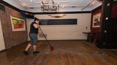 Evlin Gomez cleans flood debris at Old Fields