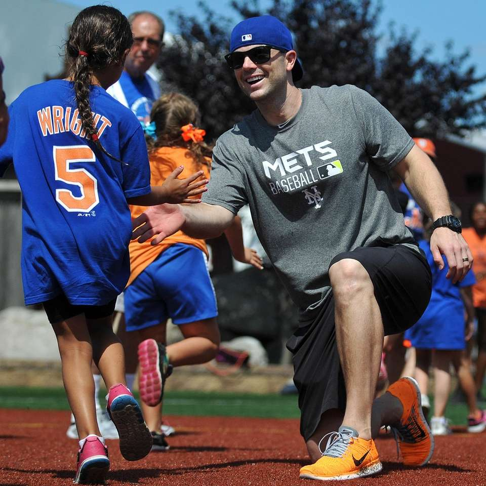 Mets captain David Wright hive-fives a fan during