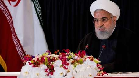 Iranian President Hassan Rouhani talks with the news