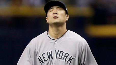 Yankees pitcher Masahiro Tanaka reacts after his throwing