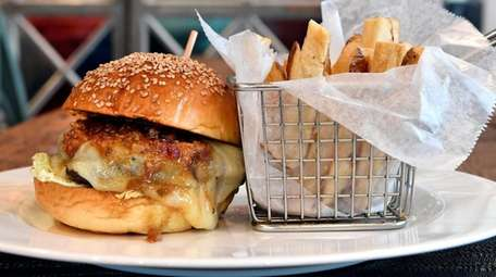 A burger with melted Cheddar cheese, mustard and