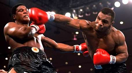 Mike Tyson, right, delivers a powerful blow to
