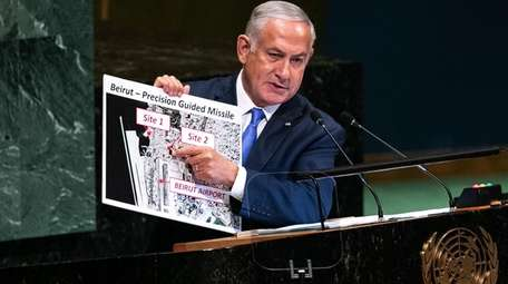 Israel Prime Minister Benjamin Netanyahu holds up a