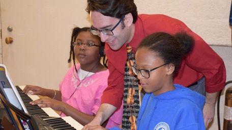 Music teacher Andrew Tilles listens to student Jordan