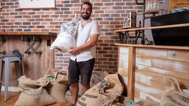 Arsalan Pourmand, owner of Flux Coffee, stands among