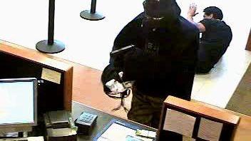 A gun-wielding man wearing a Darth Vader mask