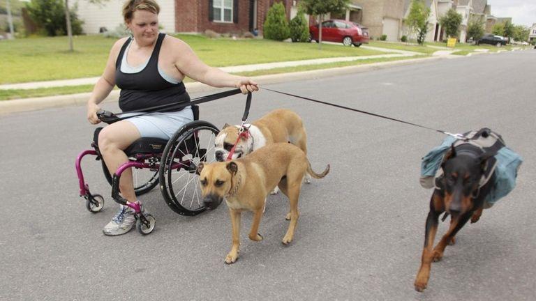 Tara Hutchinson, 33, walks her dogs Thursday in