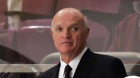 Lou Lamoriello stands behind the bench during a