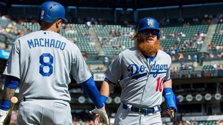 The Dodgers' Justin Turner celebrates with Manny Machado