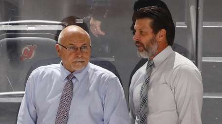 Barry Trotz and assistant Lane Lambert chat during