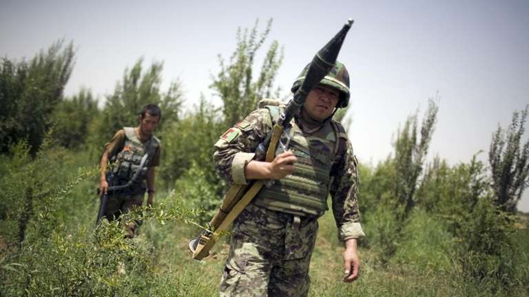 An Afghan National Army soldier carries an RPG