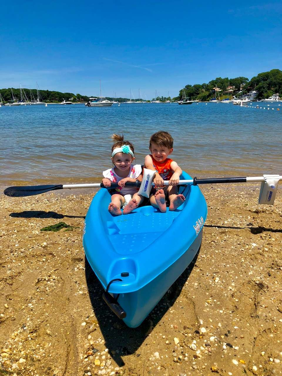 Siblings, Joseph and Sofia Woll explore a kayak
