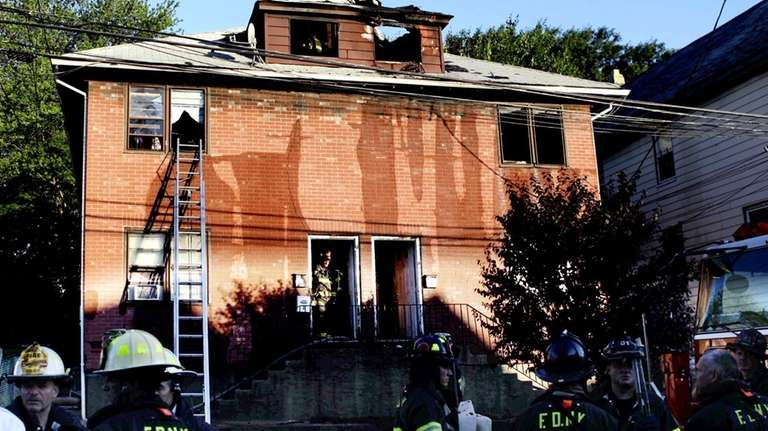 Emergency officials investigate a house fire on Staten