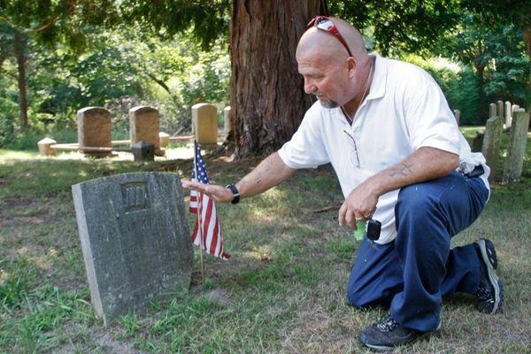 Keith Jackowski of Farmingdale touches the gravestone of