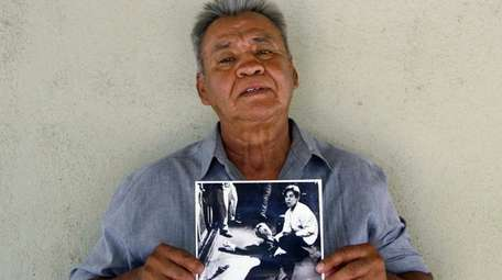 Juan Romero holding a Los Angeles Times photograph