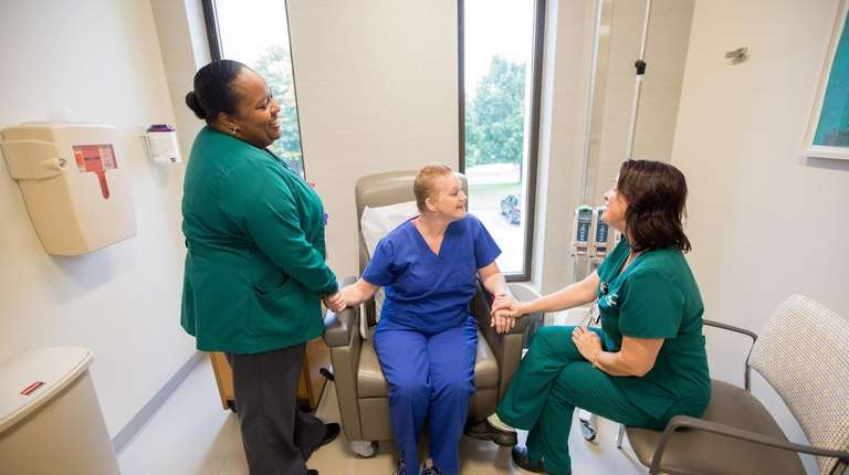 Patient Donna O'Rourke of Huntington Station, center, holds