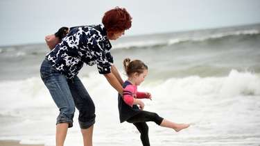 Briana Sheen, 3, of Bellmore, is lifted above