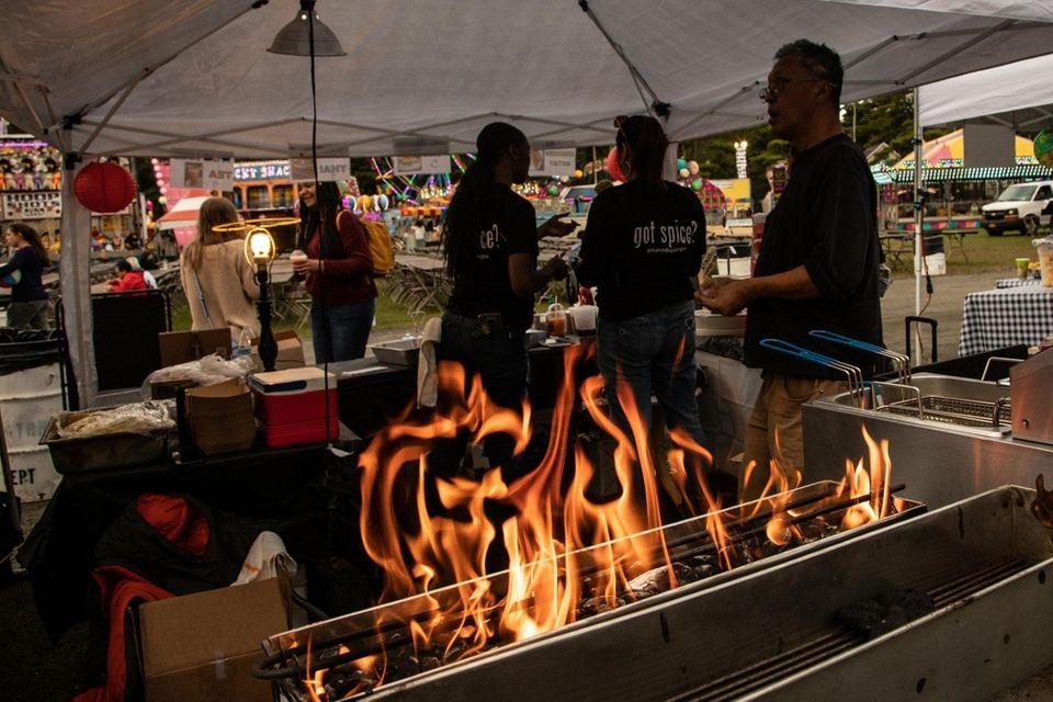 A food vendor fires up the coals, getting