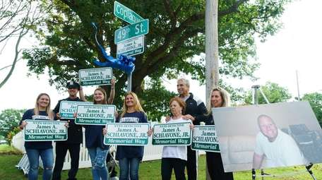 James A. Schiavone Jr.'s family holds signs bearing