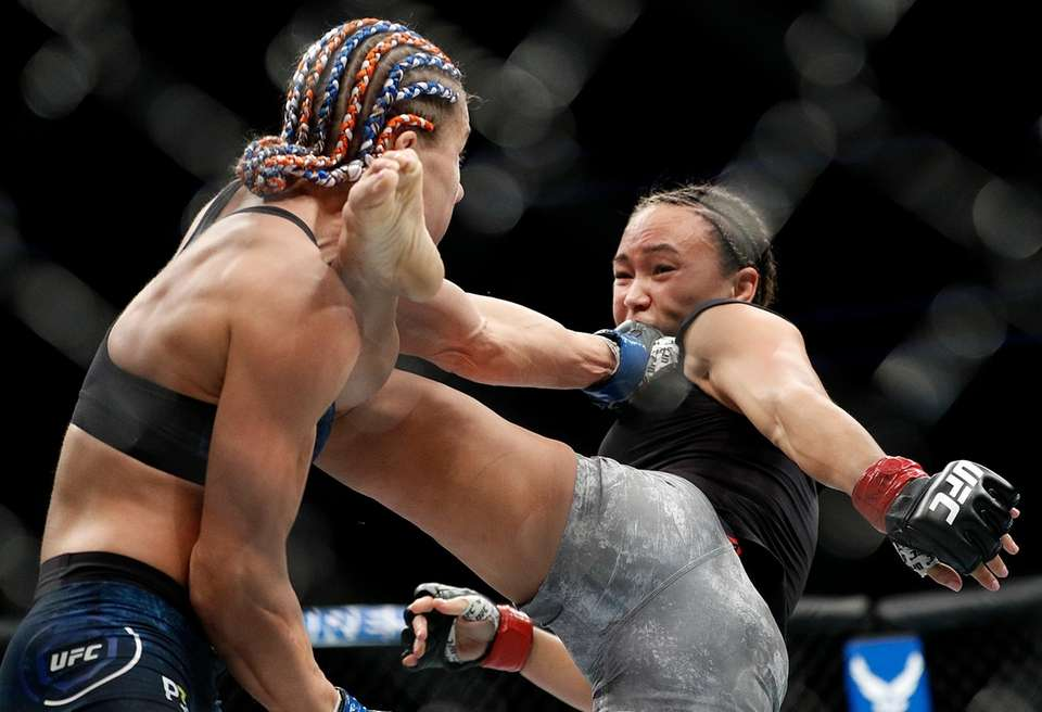 Felice Herrig punches Michelle Waterson as Waterson kicks