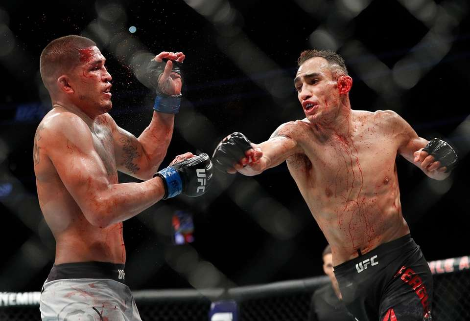 Tony Ferguson, right, punches Anthony Pettis during a