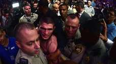 Khabib Nurmagomedov is escorted out of the arena
