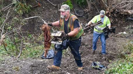 Recovery crews remove debris from the scene of