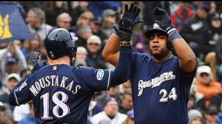 The Brewers' Mike Moustakas congratulates Jesus Aguilar after