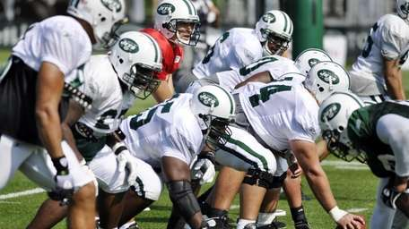 Jets quarterback Mark Sanchez, in red, directs the