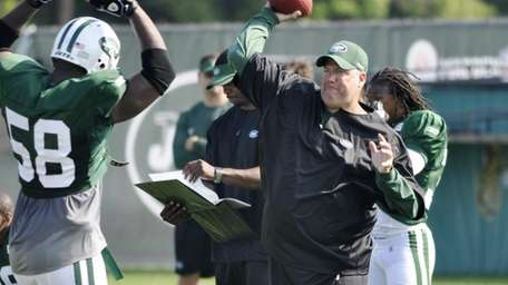 Jets head coach Rex Ryan, right, throws over