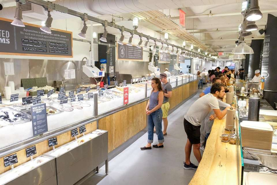 Customers select their seafood from iced displays at