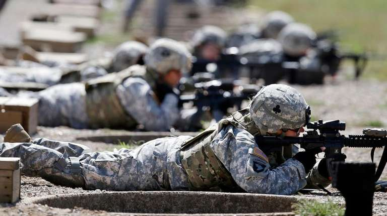 Female soldiers training on a firing range while