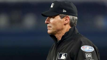 First base umpire Angel Hernandez looks on during