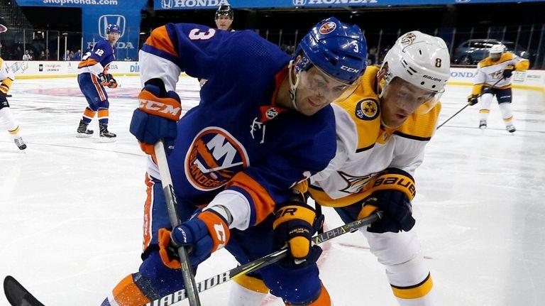 Islanders defenseman Adam Pelech battles for the puck