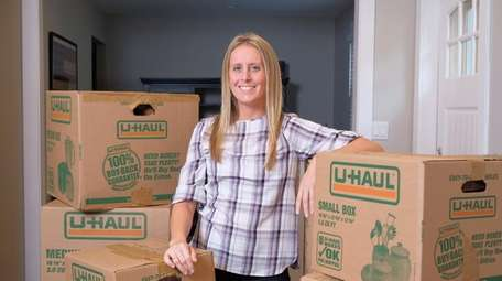 Marybeth Clark stands among a pile of boxes