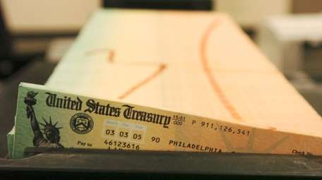 A tray of printed Social Security checks waits
