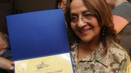 Melida Gutierrez Longle, holds a certificate that was