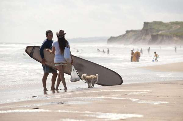 Surfers and beachgoers stroll the beach at Ditch