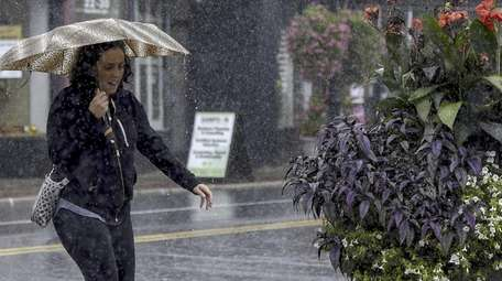 A woman battles the rain as she walks