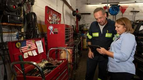 Mechanic Teddy Ott talks with Angel McCabe, president
