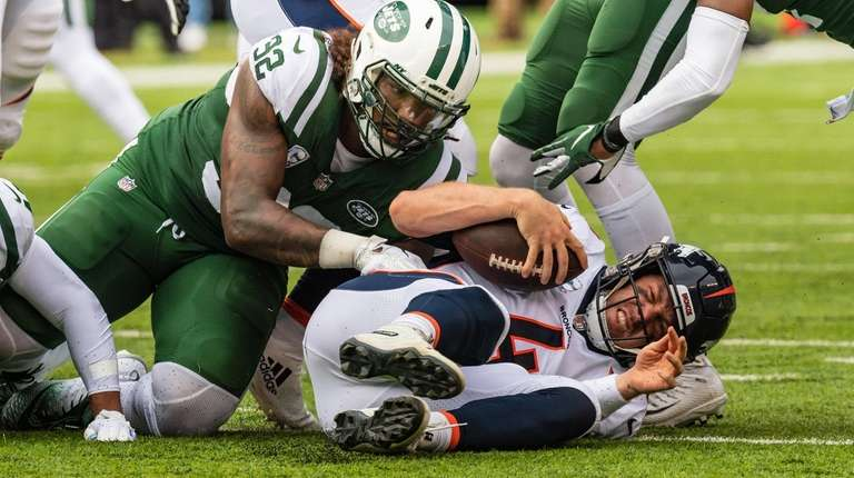 Broncos quarterback Case Keenum is sacked by Jets