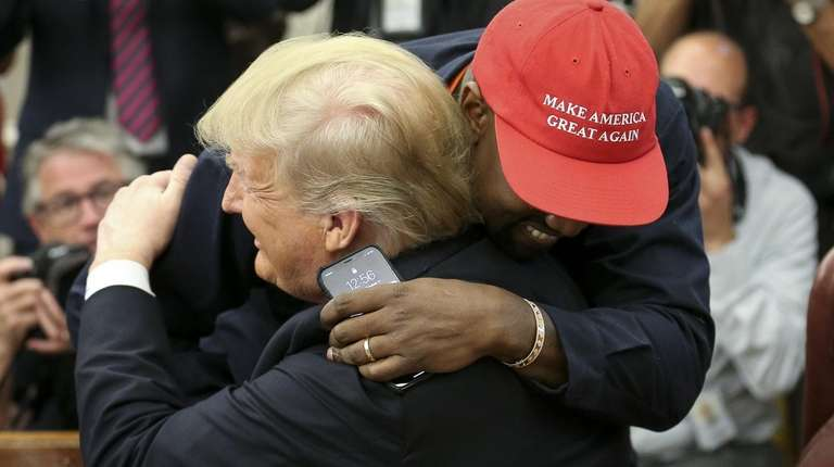 President Donald Trump hugs rapper Kanye West during