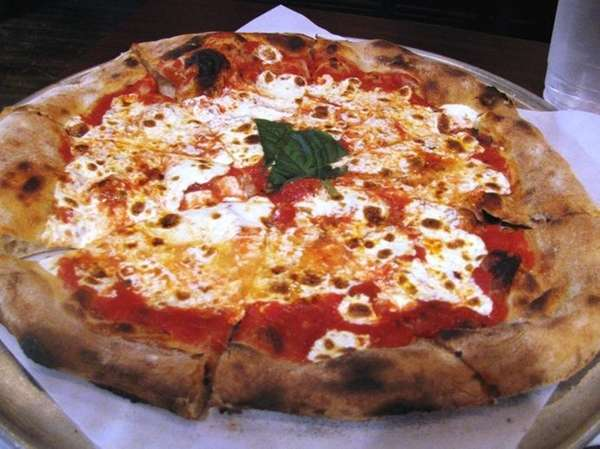 Margherita pizza is served at Grana Wood-Fired Pizza