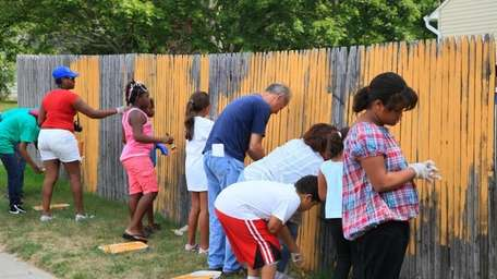 Volunteers paint over a fence during