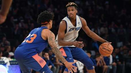 Frank Ntilikina is guarded by Trey Burke during
