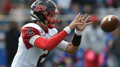 Dan Villari ,Plainedge quarterback, takes a snap during