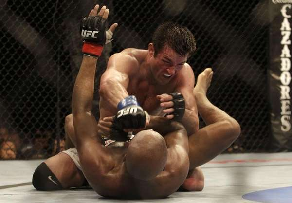Chael Sonnen, top, punches Anderson Silva during a