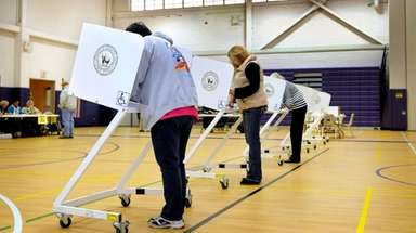 Voters cast their ballots in the gymnasium at