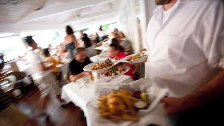 Waiters serve dishes to a packed house at