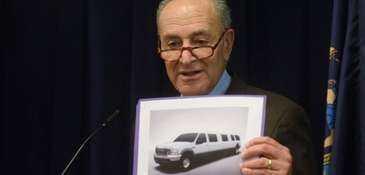 Sen. Chuck Schumer holds a picture of a